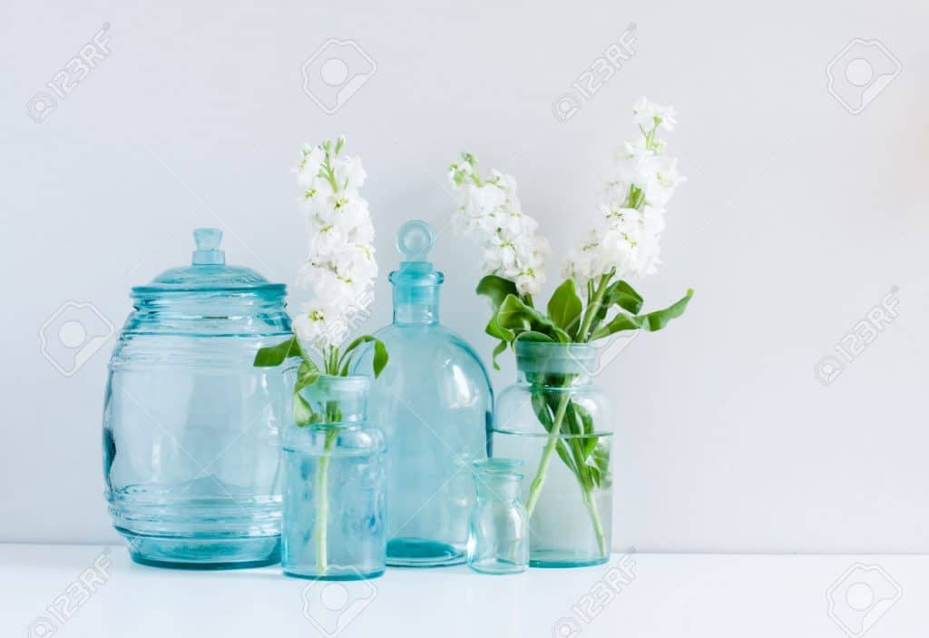 30147573 Vintage home decor background white matthiola flowers in different blue glass bottles vases and anti Stock Photo